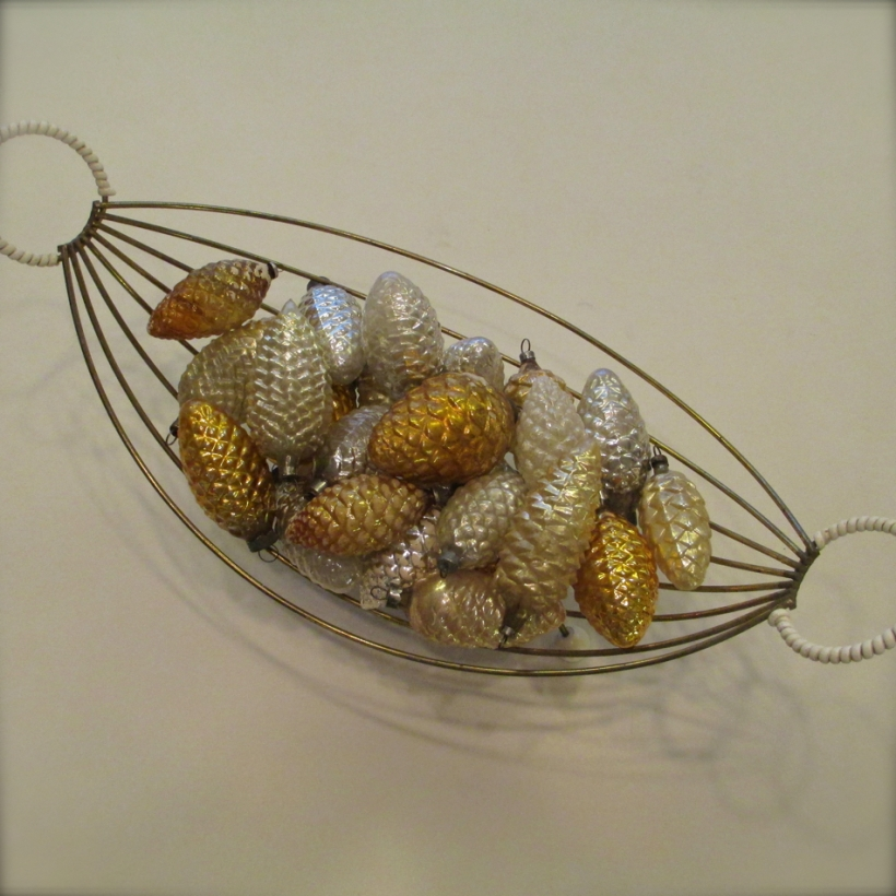 A 1950's fruit bowl filled with old glass pinecone ornaments in silvers and golds.