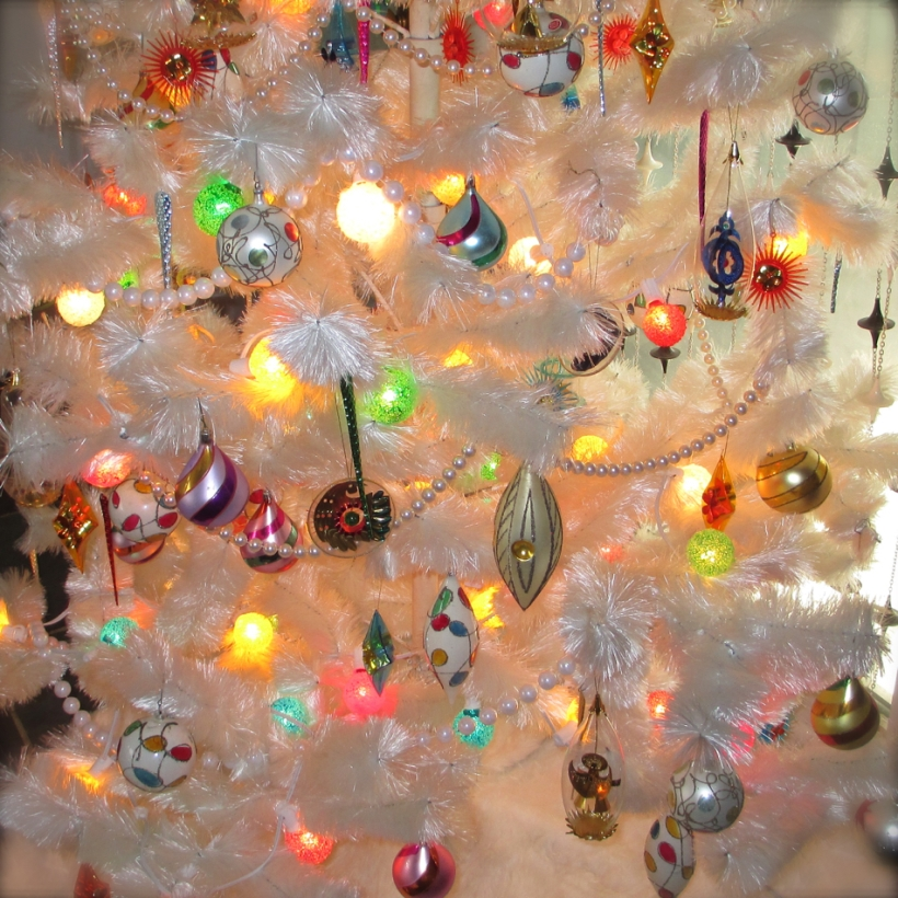 "Our ""Mod"" fiberglass tree was reworked with late 60's plastic diamonds and starbursts as well as vintage modern Resl Lenz glass and foil ornaments . 1950's aluminum icicles add sparkle and some ""spinners"" float above the GE Lighted Ice bulbs."